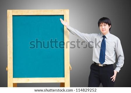Asian business man showing blank chalkboard - stock photo