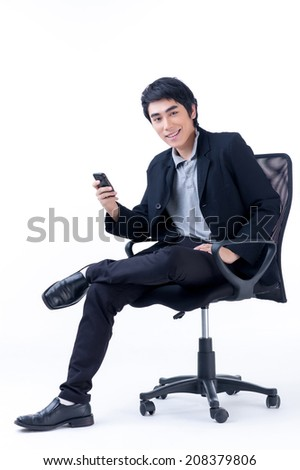Asian business man sitting and holding a cell phone on white background - stock photo