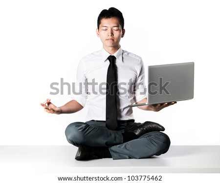 Asian Business man sitting in lotus position sitting on desk.