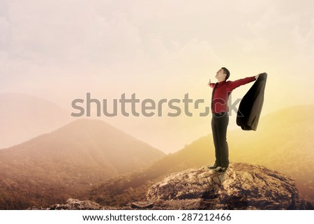 Asian business man standing on the top of mountain, raise hand and open his suit - stock photo
