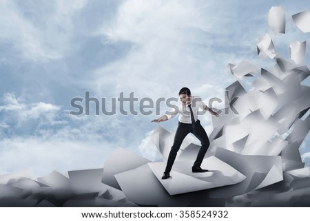 Asian business man surfing on the wave of papers. Business challenge concept - stock photo