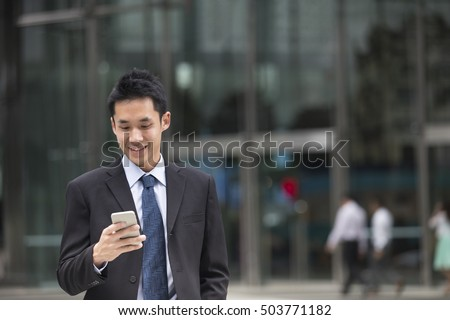 Asian business man talking reading his smart phone.
