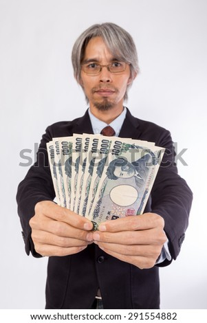 Asian Business man with Japan Money (yen) , focus at banknote soft blur at face - stock photo