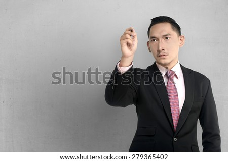 Asian business man write something over grunge wall