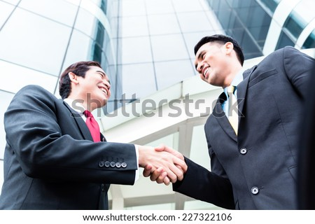 Asian business men outside in front of tower building shaking hands  - stock photo