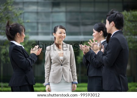 Asian business people applauding a colleague. Image depicting success and achievement. - stock photo