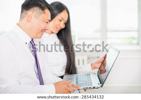 Asian business people dressed in white shirts analyze their work on the laptop at the office - stock photo