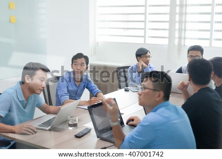 Asian business people group meeting room collaboration laptop colleagues discussing conference desk real office software developer team - stock photo