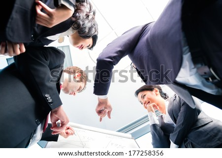 Asian business people in group structuring deal on flipchart - stock photo