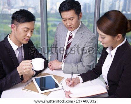 asian business people meeting in office, looking serious. - stock photo