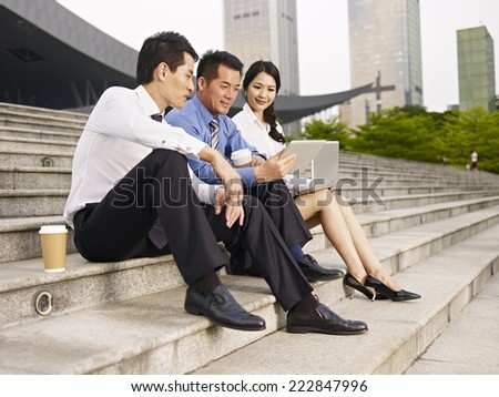 asian business people sitting on steps and looking at tablet computer. - stock photo