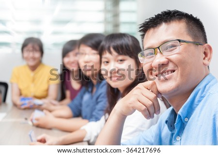Asian business people team happy smile man face, group businesspeople sitting at desk real office - stock photo