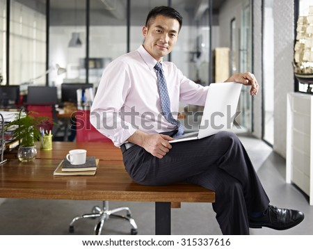 asian business person sitting on desk holding laptop computer in office. - stock photo