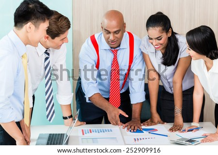 Asian business startup team in meeting discussing plan, figures, and ideas - stock photo