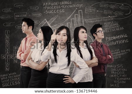 Asian business team in front of blackboard with success formula - stock photo