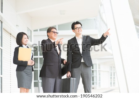 Asian business team meeting, pointing over and having discussion. Modern office background.