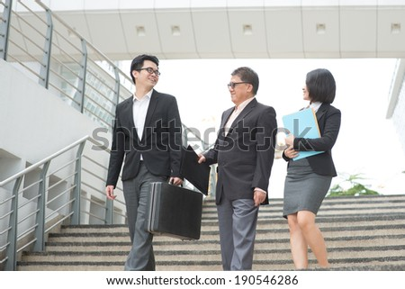 Asian business team meeting, walking and having discussion.