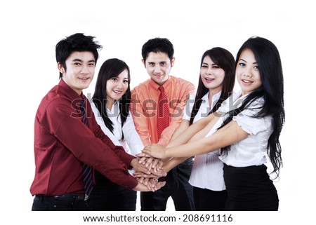Asian business team showing unity by joining their hands together - isolated on white - stock photo