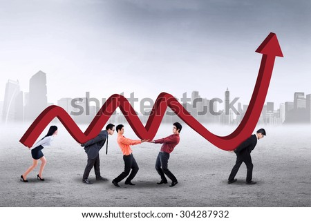 Asian business team walking outdoors while carrying a business chart together - stock photo