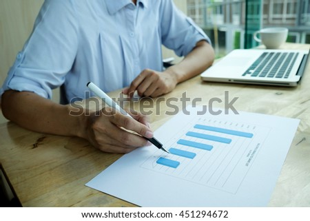 Asian business woman discussing data on chart and using her new modern computer for calculation or analysis. Business concept. - stock photo