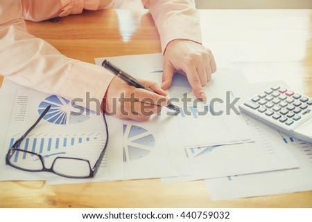 Asian Business woman hand pointing at business document during discussion at meeting and  using a calculator to calculate the numbers.Vintage tone - stock photo