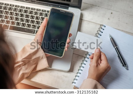 Asian business woman holding a credit card and using laptop for online shopping.