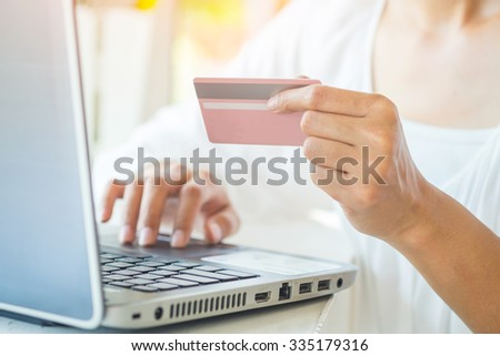 Asian business woman holding a credit card and using laptop for online shopping.(selective focus) - stock photo