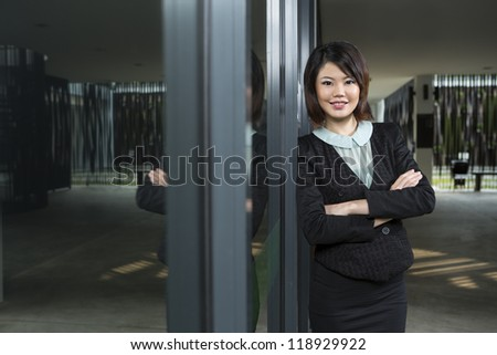 Asian Business woman leaning against a window. - stock photo
