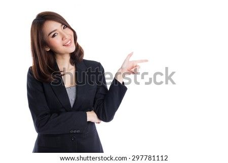 Asian Business woman pointing to copyspace on white background - stock photo