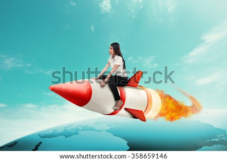 Asian business woman riding rocket across the earth - stock photo