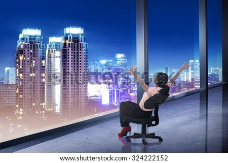 Asian business woman sii on chair looking at the city. Business success concept - stock photo