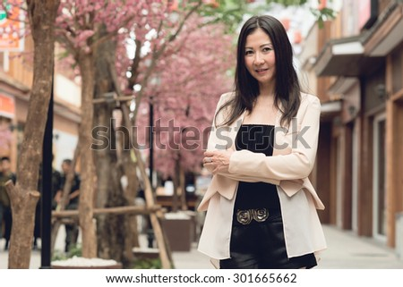 Asian business woman standing on the street - stock photo