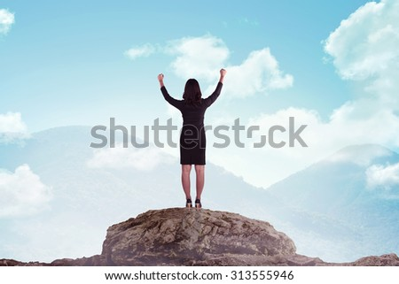Asian business woman standing on the top of the mountain. Business success concept