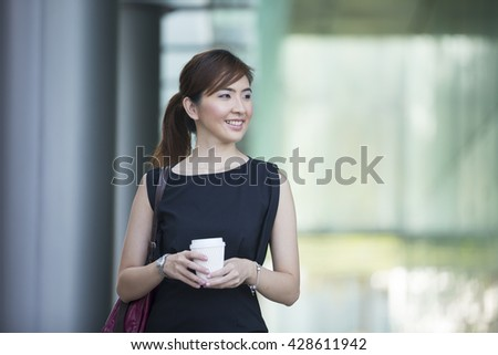 Asian business woman standing outside with office buildings in the background.