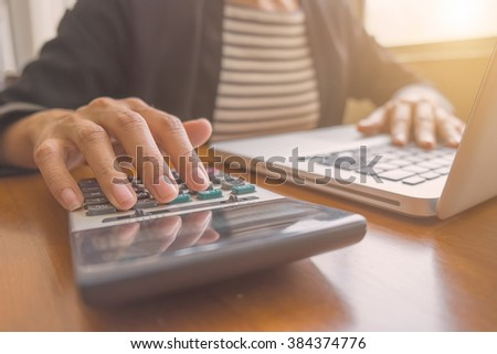 Asian business woman using calculator and laptop for online shopping .vintage tone Retro filter effect,soft focus,low light.(selective focus)