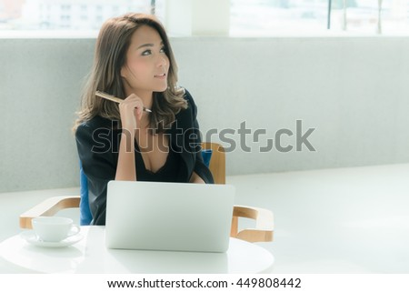 Asian business woman using laptop  with pen in hand while looking at something in the office in the office - stock photo