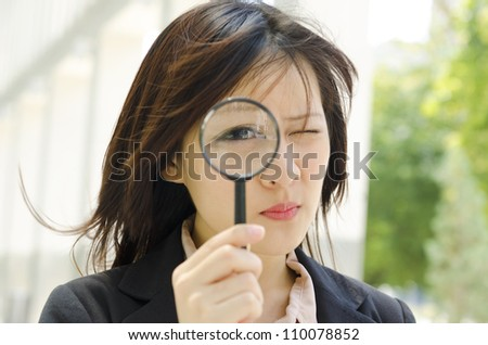 Asian business woman with magnifying glass to the eye - stock photo