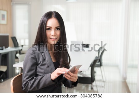 Asian business woman with smart phone and checking her email texting, messaging, using smartphone application with touch screen technology in office, business concept.