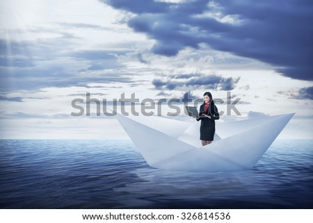 Asian business woman working with laptop on the paper boat, sailing on the sea