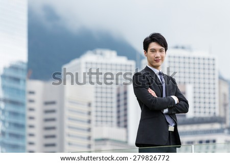 Asian businessman arm cross with business background - stock photo