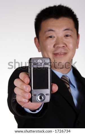Asian businessman displaying mobile phone. (focus on phone) - stock photo