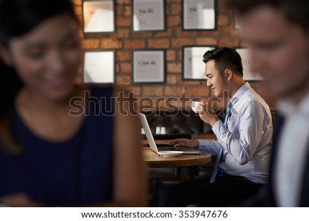 Asian businessman drinking coffee and using laptop in cafe