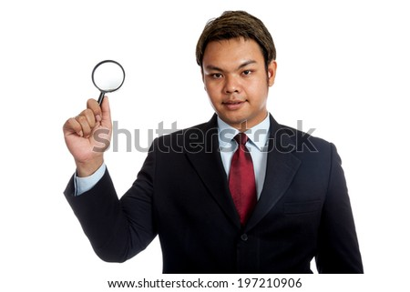 Asian businessman hold a  magnifying glass isolated on white background