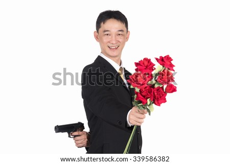 Asian businessman holding a gun and roses, The social mask, Every social has to wear a mask together. Don't believe what you see. - stock photo