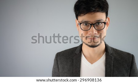 Asian businessman in black suit with grey background.