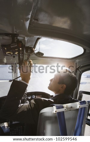 Asian businessman in helicopter - stock photo
