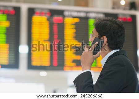 Asian Businessman looking at airport flight timetable and on the phone. - stock photo