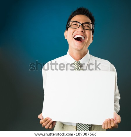 Asian businessman loudly laughing while holding an empty board - stock photo