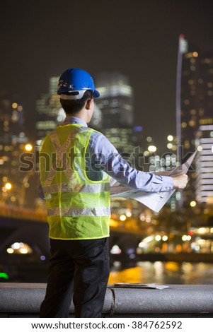 Asian businessman outdoors using his Smart phone at night in modern city. Working late and Business on the go concept.