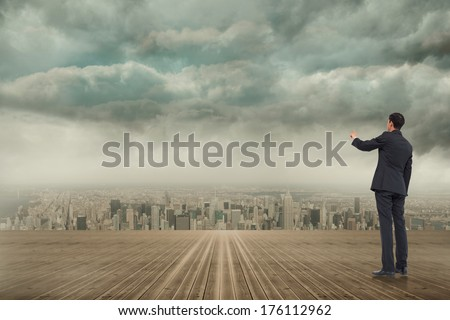 Asian businessman pointing against cityscape on the horizon